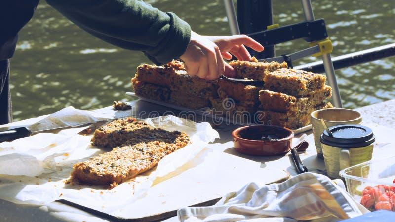 Mains du ` s de femme découpant le gâteau en tranches à la stalle A de boulangerie du marché image stock