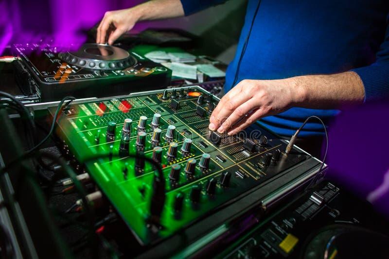 Mains du ` s du DJ au mélangeur de musique à une partie photos libres de droits
