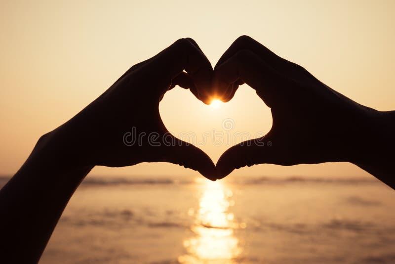 Mains effectuant une forme de coeur photo stock