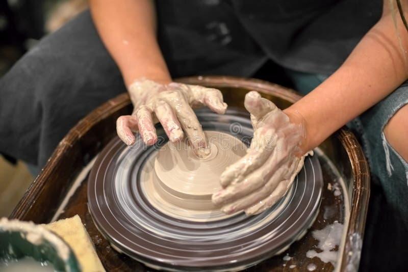 Mains en argile sur le fond d'une roue de potiers tournante photos stock