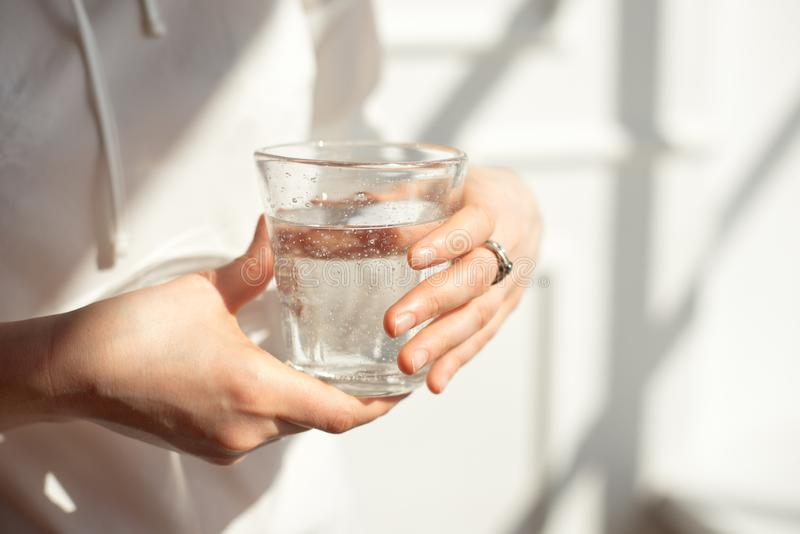Mains en gros plan de fille dans les supports de bureau à la lumière du soleil tenant un verre d'eau propre entre le travail photographie stock libre de droits