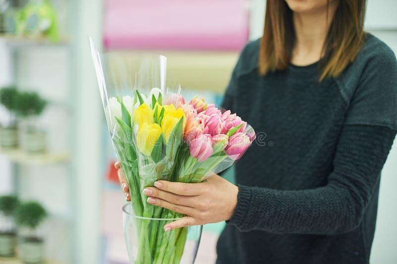 Mains en gros plan de fleuriste avec des fleurs Fleuriste tenant le bouquet de floraison des tulipes roses sur un fond de toile photos libres de droits