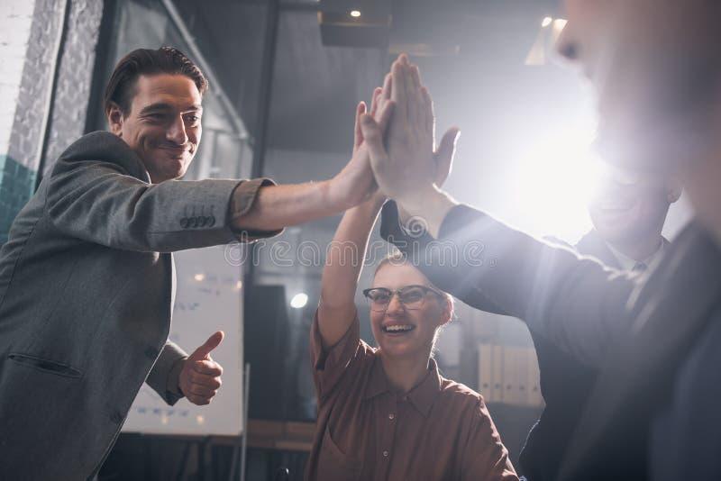 Mains en hausse d'heureuse équipe de démarrage dans la pyramide photographie stock libre de droits