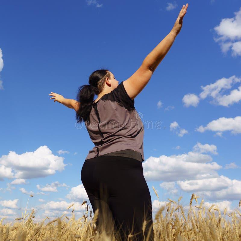 Mains en hausse de femme de poids excessif, vue du dos photos stock
