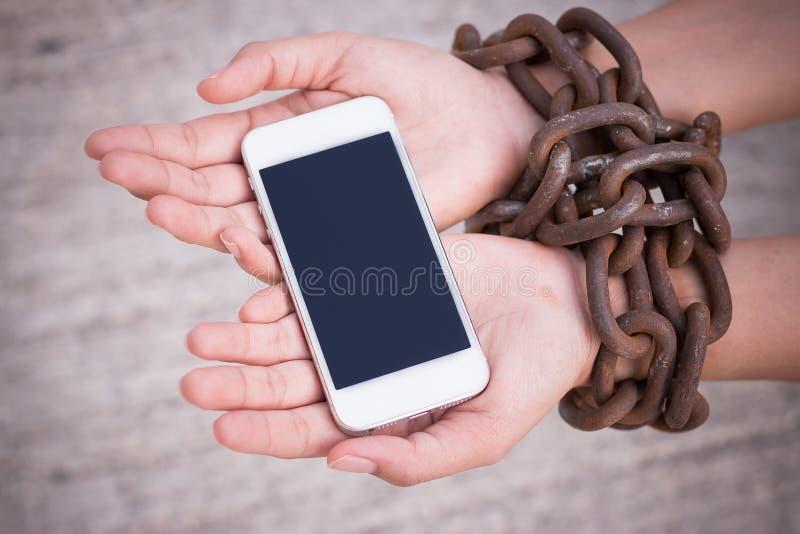 Mains enchaînées tenant le smartphone images libres de droits