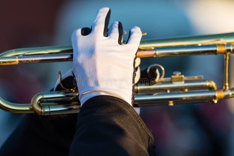 Mains enfilées de gants d'un trompettiste dans une fanfare photographie stock libre de droits