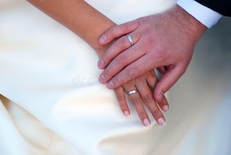 Mains entrelacées avec des anneaux de mariage image stock