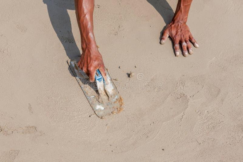 Mains et ombre mobiles du travailleur de maçon employant le plast en acier de truelle photo stock