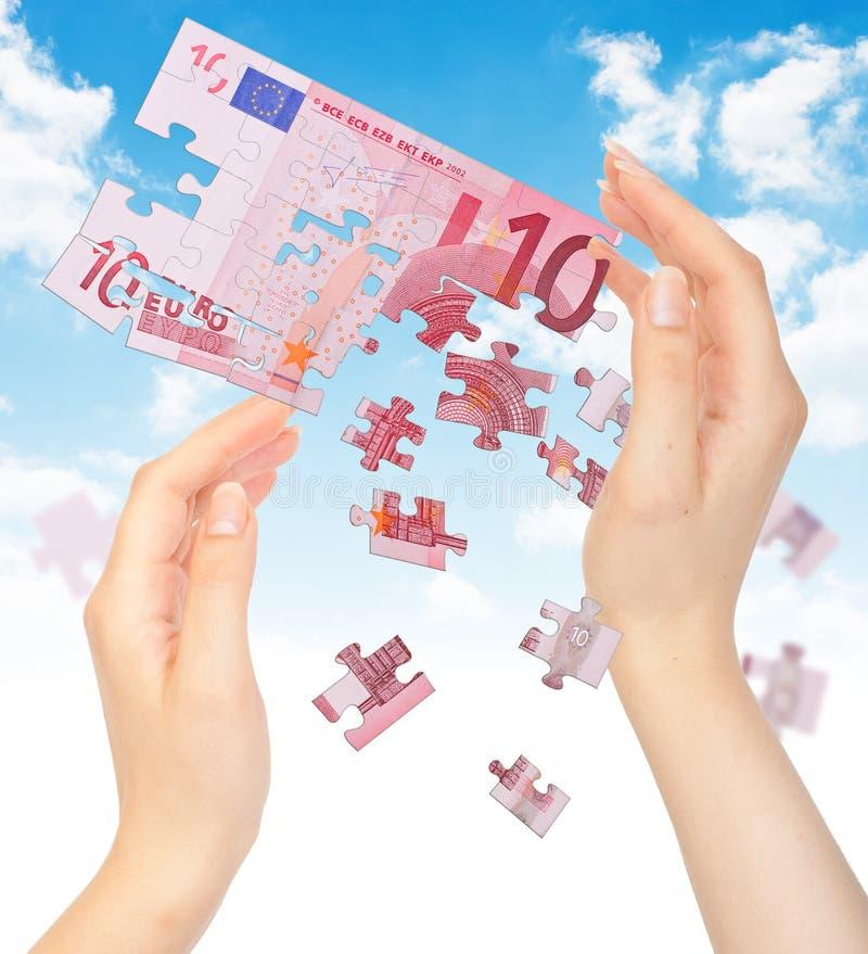 Mains et puzzle hors de l'EURO d'argent photos stock
