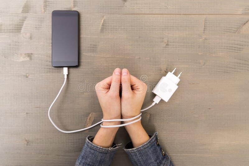 Mains et smartphone femelles Le ` s de femme remet o emprisonné et enveloppé image stock
