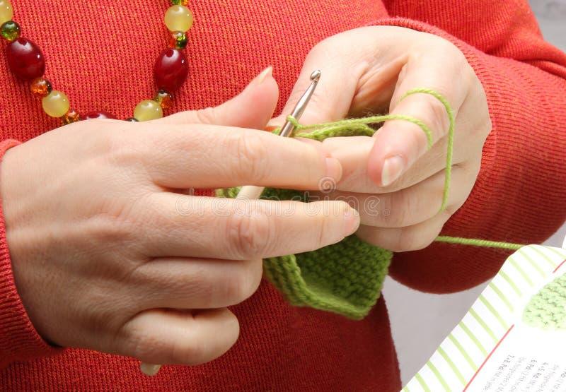 Mains faisant du crochet avec le fil vert image stock