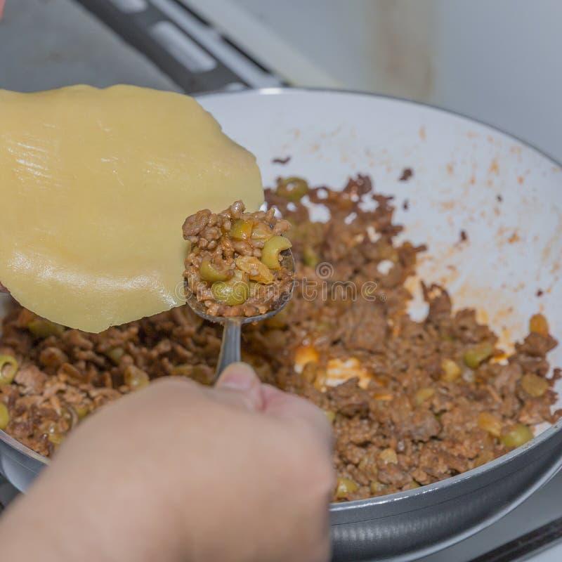 Mains femelles administrant le boeuf à la cuillère haché préparé avec des olives sur la pâte crue fraîche d'un empanada photo stock