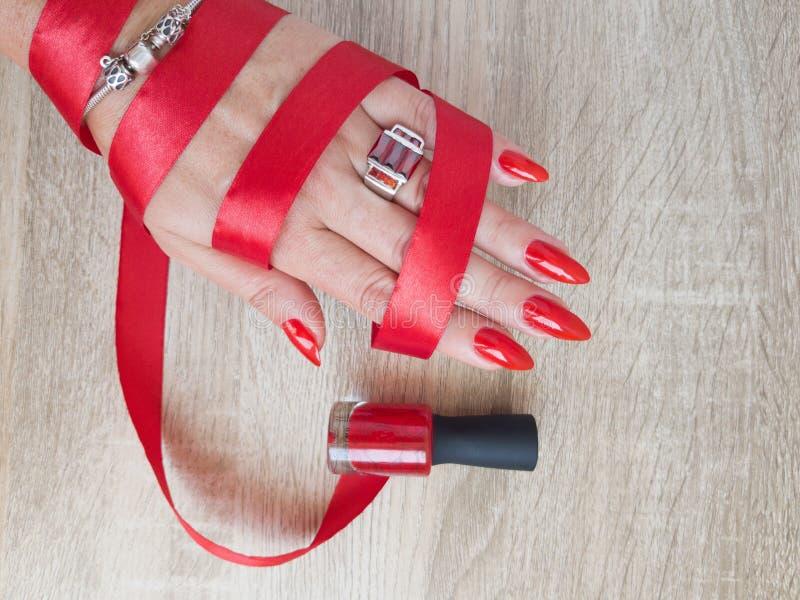 Mains femelles avec de longs ongles avec le vernis à ongles rouge image stock