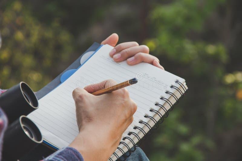 Mains femelles avec l'écriture de crayon sur le carnet photo stock