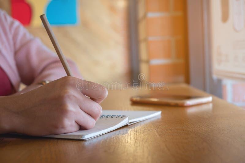 Mains femelles avec l'?criture de crayon sur le carnet photo libre de droits