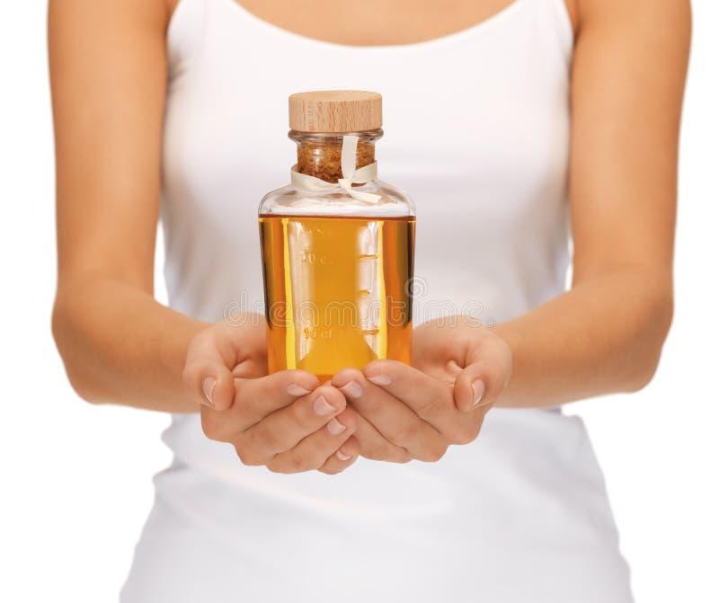 Mains femelles avec la bouteille d'huile image libre de droits