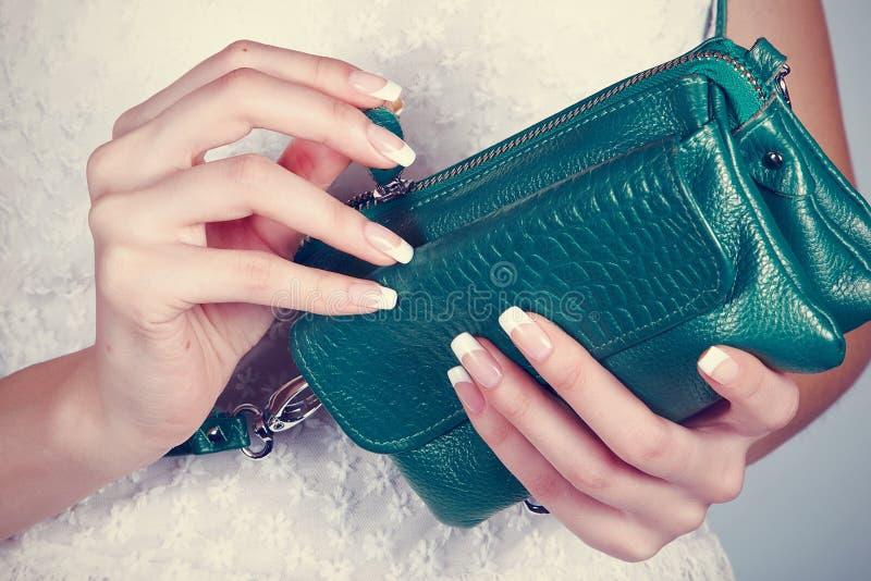 Mains femelles avec la manucure avec le sac à main images stock