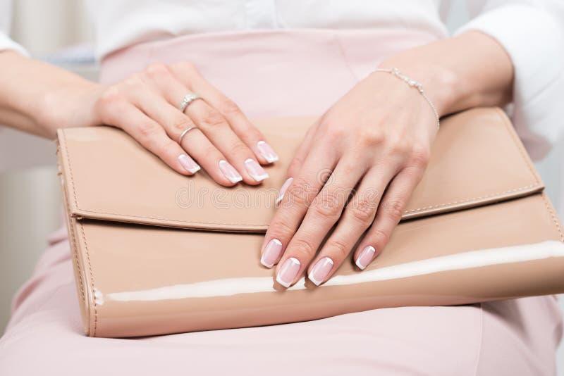 Mains femelles avec la manucure française tenant le sac en cuir image stock
