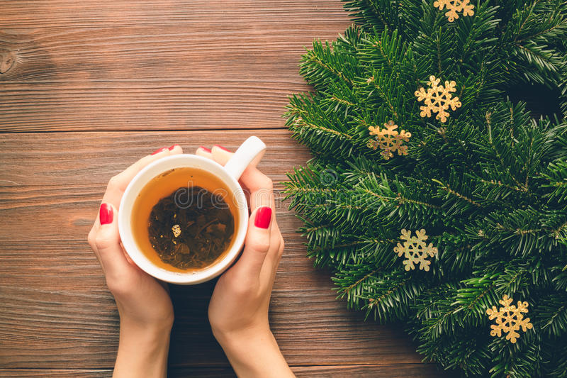 Mains femelles avec la manucure rouge tenant une tasse de thé sur un backgro photos libres de droits