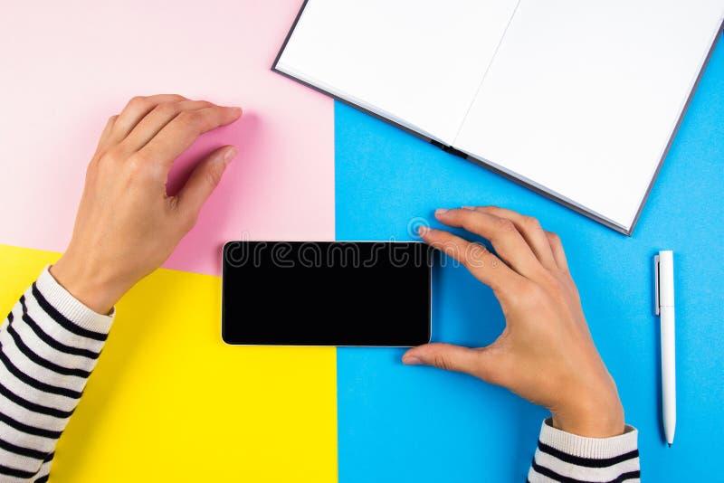 Mains femelles avec le téléphone intelligent mobile et le carnet ouvert au-dessus du fond jaune, bleu et rose photographie stock libre de droits