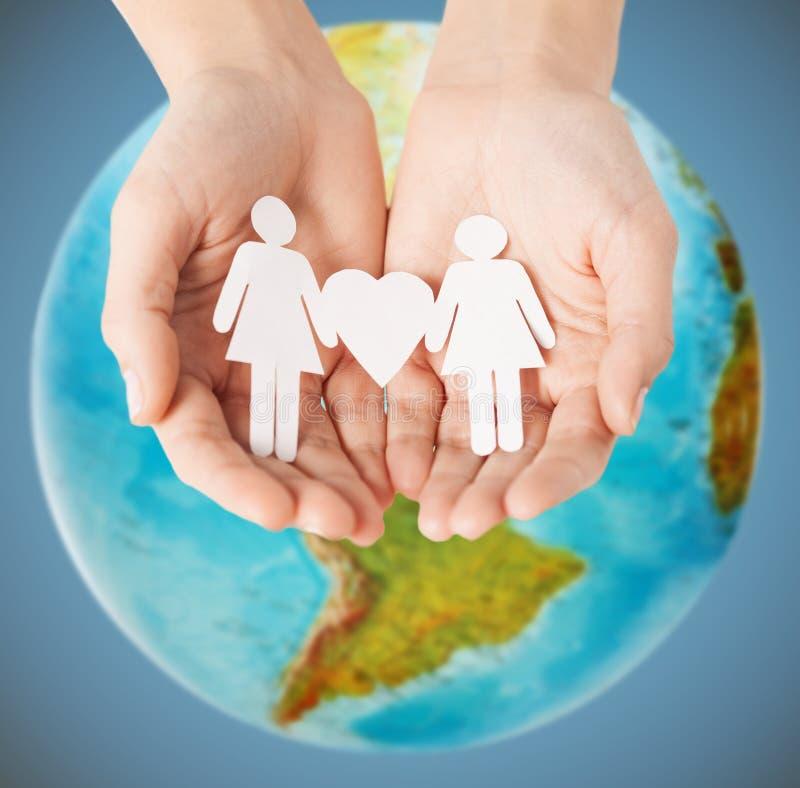 Mains femelles avec les chiffres gais de papier de couples photos stock