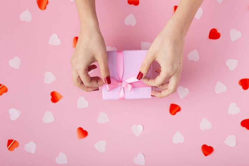 Mains femelles avec un boîte-cadeau sur une vue supérieure colorée en pastel de fond, la fille ouvrant un présent et déliant un a photos libres de droits