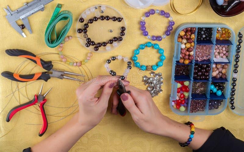 Mains femelles avec un outil sur un fond jaune Fabrication du bracelet des perles colorées photo libre de droits
