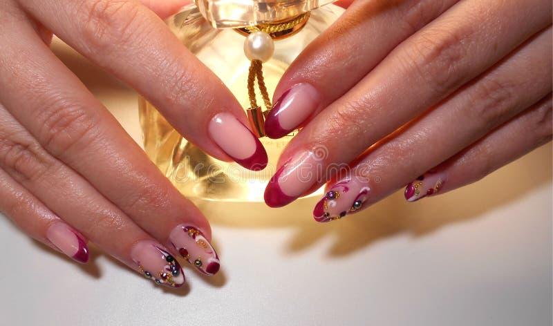 Mains femelles avec une bouteille de parfum photographie stock