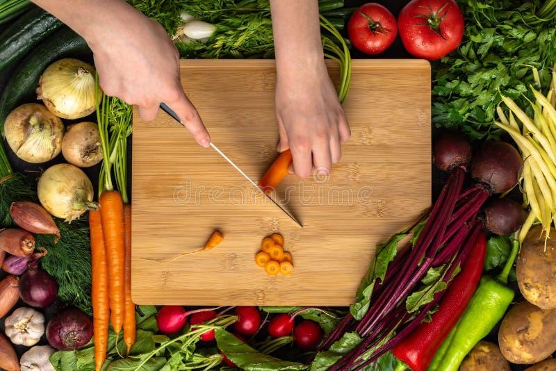 Mains femelles coupant la carotte organique avec le chef Knife sur le hachoir en bois photo stock