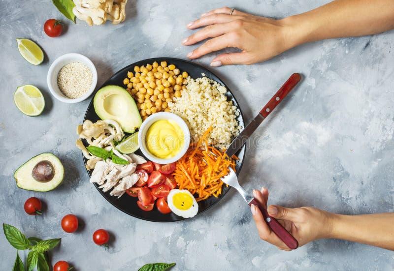 Mains femelles Cuvette saine de déjeuner de vegan sur le fond concret photos libres de droits