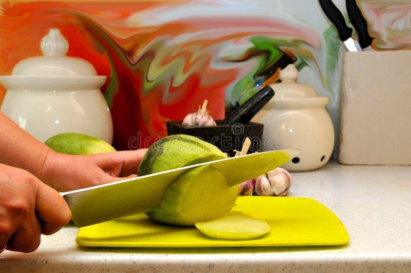 Mains femelles découpant en tranches avec un grand couteau de cuisine photos stock
