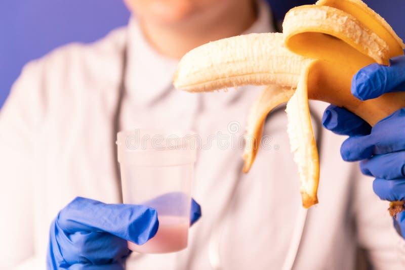 Mains femelles de médecins dans les gants bleus médicaux tenant un récipient en plastique avec le sperme et une banane photo stock