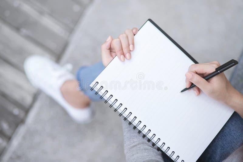 Mains femelles de vue supérieure avec l'écriture de stylo sur la séance de bloc-notes de carnet photos libres de droits