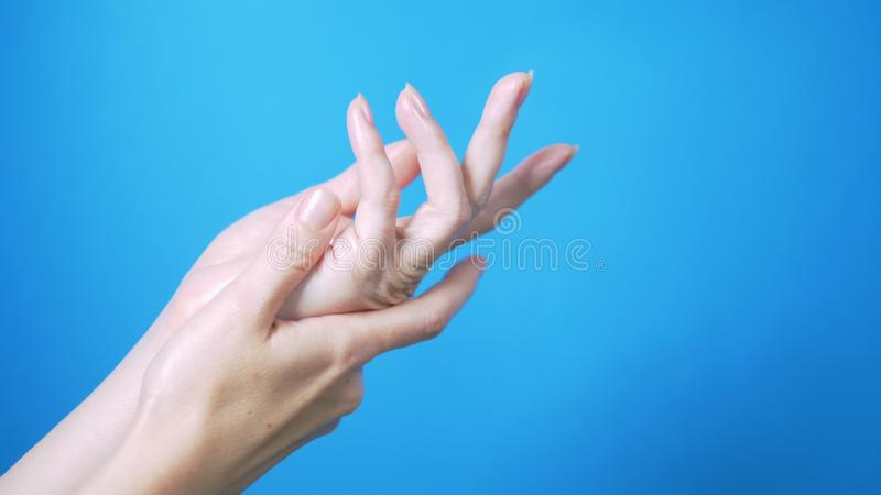 Mains femelles douces avec le mouvement naturel de manucure admirablement sur un fond bleu Place pour le texte photos stock