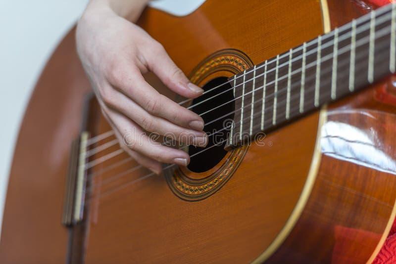 Mains femelles jouant la guitare photo stock