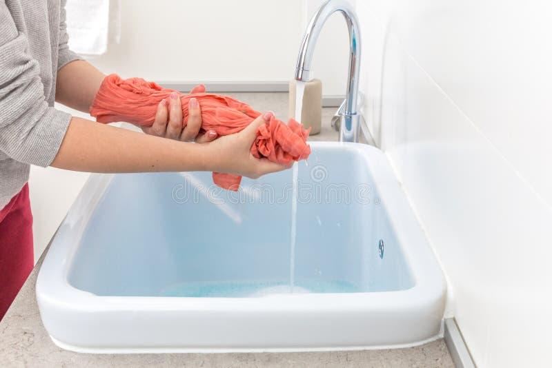 Mains femelles lavant des vêtements de couleur dans l'évier photo libre de droits