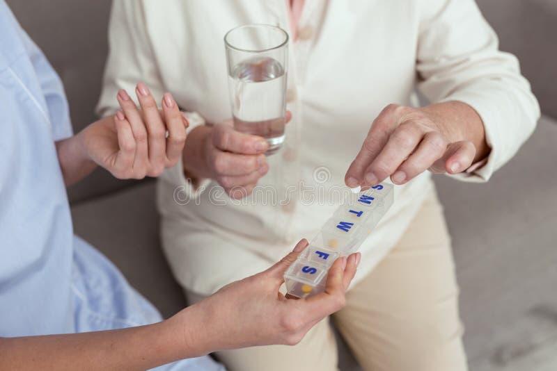 Mains femelles mûres prenant des pilules de récipient photo stock