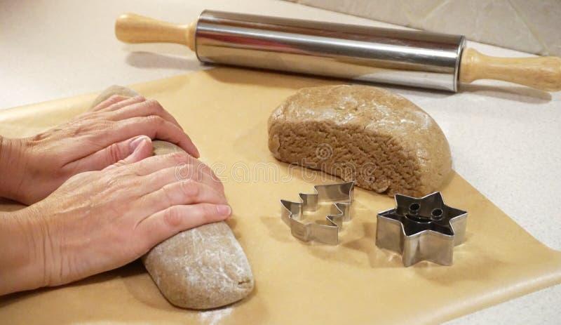 Mains femelles malaxant la pâte de pain d'épice pour le gâteau de Noël images libres de droits
