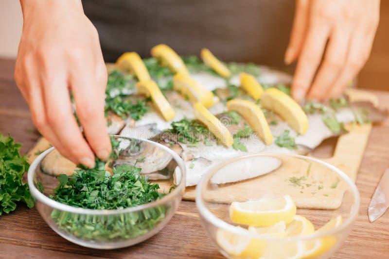 Mains femelles préparant des poissons avec les citrons et la verdure images libres de droits