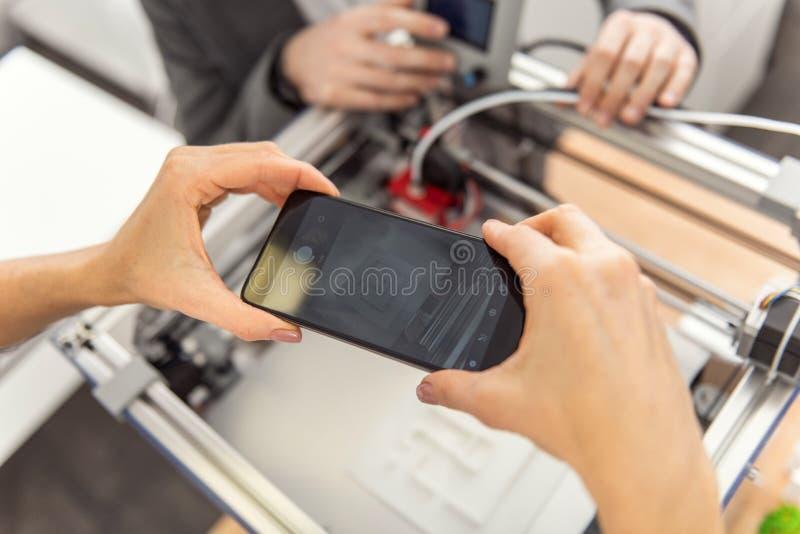 Mains femelles prenant la photo de l'imprimante 3D créant le modèle photographie stock libre de droits