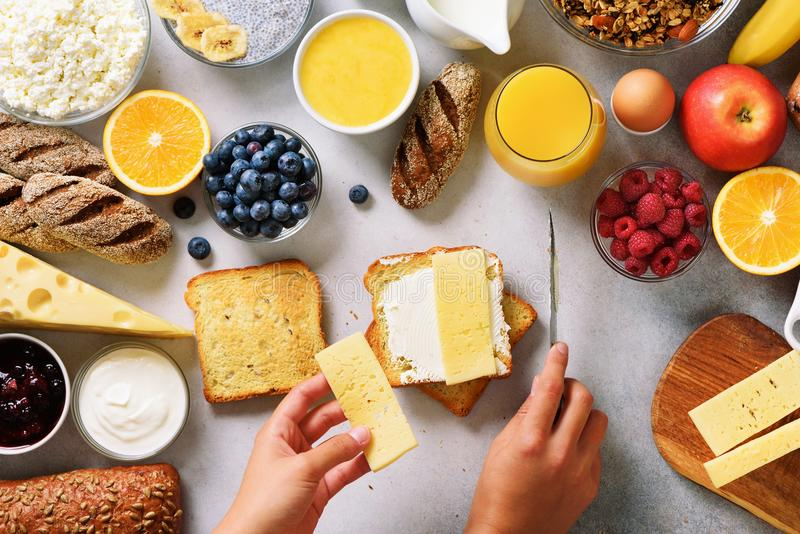 Mains femelles répandant le beurre sur le pain Femme faisant cuire les ingrédients sains de petit déjeuner de petit déjeuner, cad photographie stock libre de droits