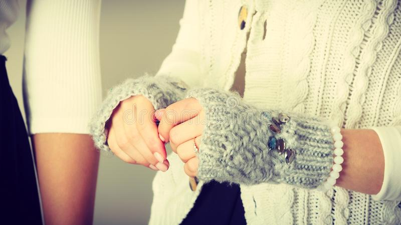 Mains femelles sensibles avec les gants gris images stock