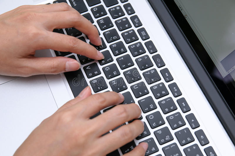 Mains femelles sur l'ordinateur portatif photo stock