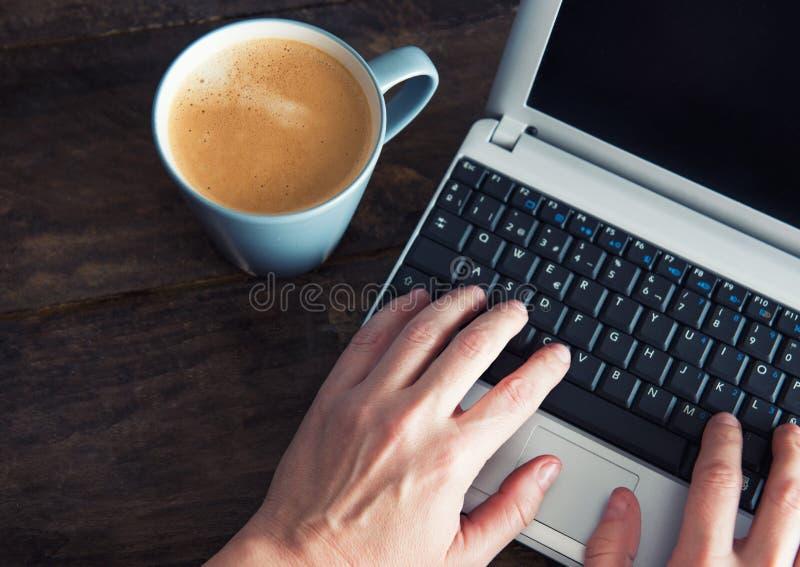 Mains femelles sur un ordinateur et un café sur un fond en bois photographie stock