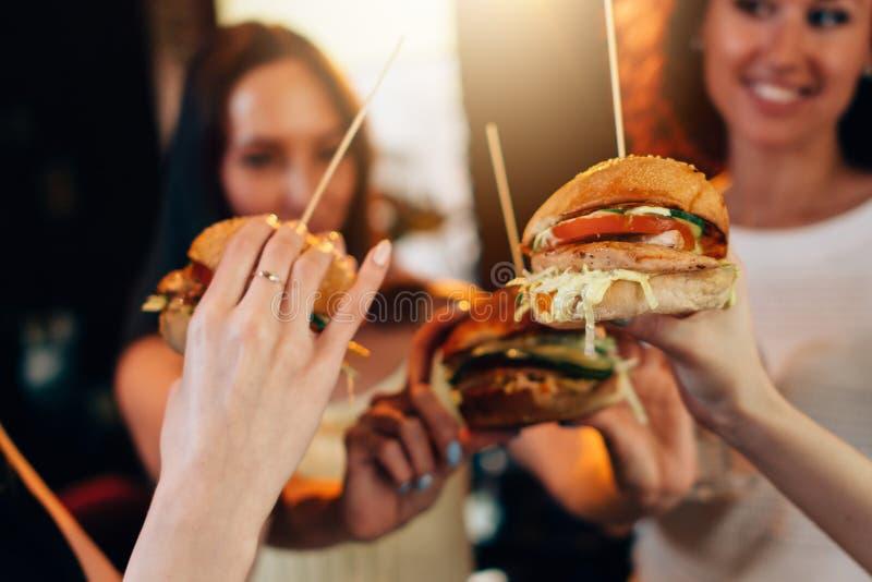 Mains femelles tenant de grands hamburgers juteux savoureux avec les femmes brouillées à l'arrière-plan image libre de droits