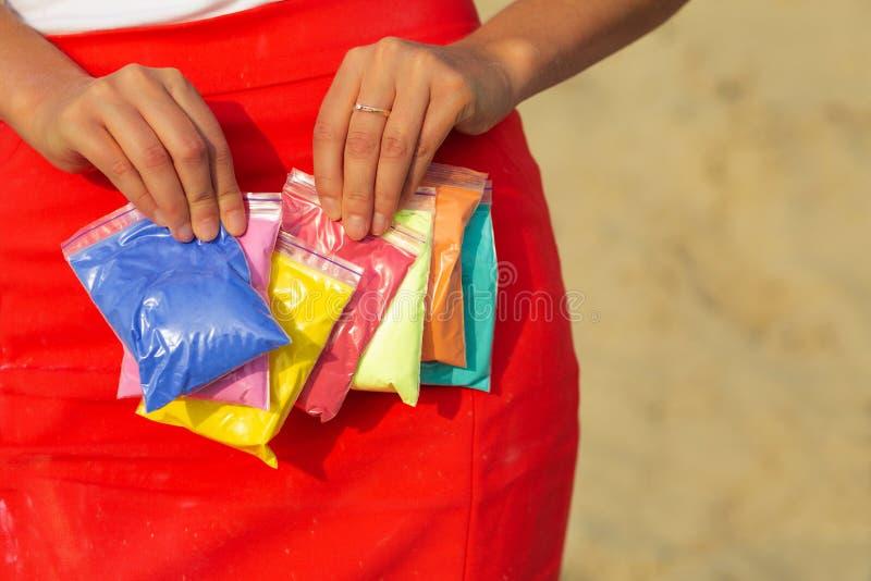 Mains femelles tenant des sacs de peinture colorée sèche Holi Spac vide photos libres de droits