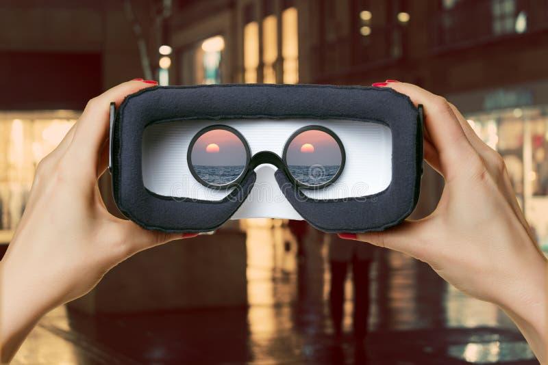 Mains femelles tenant des verres de réalité virtuelle photo stock