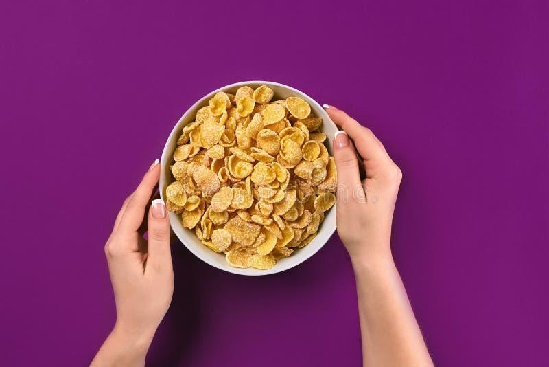Mains femelles tenant la cuvette avec le petit déjeuner sain, plan rapproché Cuvette avec des cornflakes sur le fond coloré images libres de droits