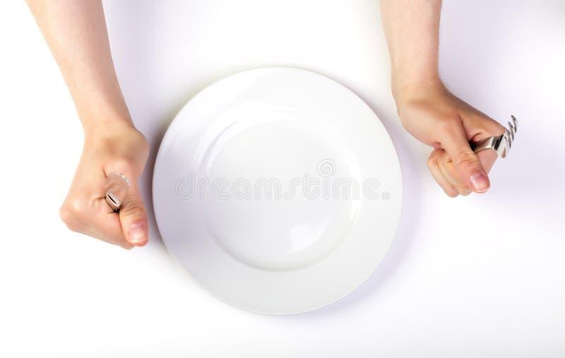 Mains femelles tenant la fourchette et le couteau à côté d'un plat vide images stock
