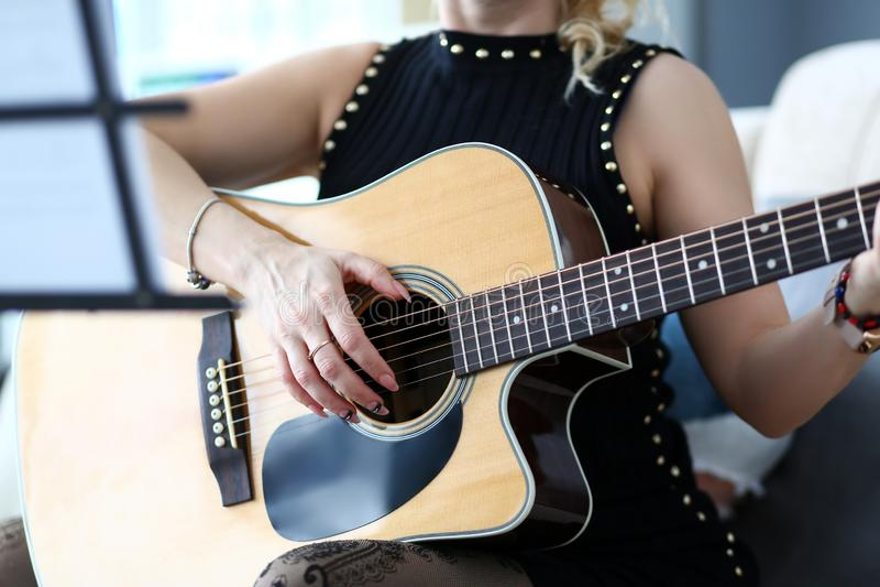 Mains femelles tenant la guitare acoustique occidentale se reposant sur le divan à la maison images stock